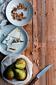 Cotton sack with fresh pears, plate with cheese and walnuts