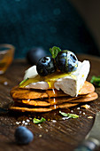 Camembert Cheese on savoury biscuits with honey and blueberries