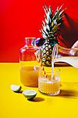 Eistee mit Ananas und Kokossirup wird in Glas eingeschenkt