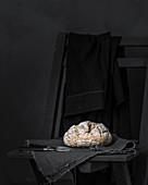 Ein hausgemachtes Brot auf Leinentuch vor schwarzem Hintergrund