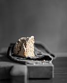 Eine Ecke frisch gebackenes Brot auf Leinentuch vor grauem Hintergrund