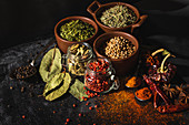 Different kinds of natural aromatic spices placed on slate surface