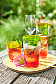 Iced tea with fruit and basil on a table in a summer garden