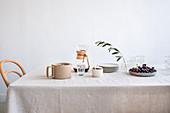 Tisch-Stilleben mit Olivenzweig und Trauben