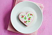 Heart cookies hand-painted with floral motifs on a plate