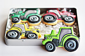 Colorfully decorated cookies in the shape of tractors for gifting in a tin