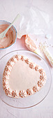 Kleiner Herzkuchen mit Cremerosetten und Zuckerperlen