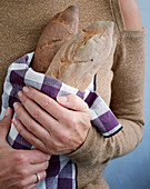 A woman holding baguettes wrapped in a cloth