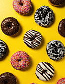 Donuts with different glazes on a yellow background