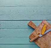Holzschneidebrett mit Brotscheibe auf rustikalem Holzuntergrund