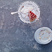 A piece of cassis cream cake on a cake stand with doilies