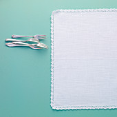 Linen tablecloth with a lace border and cake forks