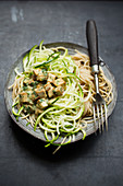 Spelt spaghetti with zucchini and tofu in sesame sauce, vegan