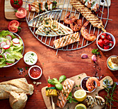 Grilled fish, shrimp and kebabs with dips, lettuce and baguettes