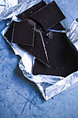 Zerbrochene dunkle Schokolade im Silberpapier