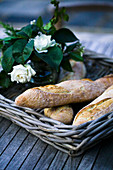Wicker tray of bread and flowers on table