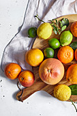 Various citrus fruits on a round wooden cutting board