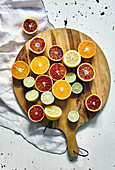 Various halved citrus fruits on a round wooden cutting board