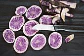 Blaue Kartoffeln der Sorte St. Galler, aufgeschnitten, mit Messer