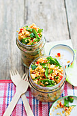 Vegan couscous salad with bell pepper and sugar snap peas in a glass jar
