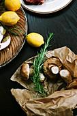 Zutatenstilleben mit Pilzen, Rosmarin und Zitronen