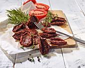 Tomaten, getrocknet und frisch, mit Thymian und Rosmarin auf Schneidebrett