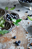 Blueberries and bay leaves in a muffin tray on a rustic surface