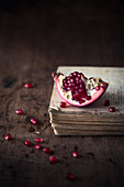 Piece of a fresh pomegranate on a wooden surface