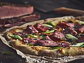 Pizza mit Pastrami und Frühlingszwiebeln