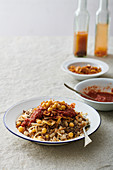Koshari Traditional Egyptian dish - vegan mixed rice, pasta, lentils, with caramelized onions and tomato chili sauce