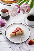 Vegan cheesecake with strawberry sauce and white, grated rice milk chocolate