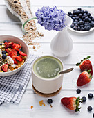 Matcha tea and muesli with almond yogurt and fresh berries