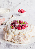 Pavlova dessert, served with mascarpone cream and fresh rasberries