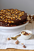 Vegan brownie cake with hazelnuts and salted caramel n white cakestand