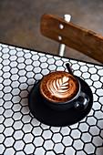 Cappuccino mit Milchschaummuster auf Bistrotisch