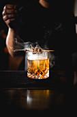 Dampfender Cocktail mit Spießchen auf Bartheke