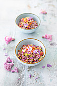 Low carb rice salad made from colorful cauliflower, peppers and edible flowers (vegan)