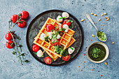Gluten-free waffles made from red lentil flour with tomato, mini mozzarella and wild garlic pesto