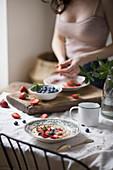 Frau am Frühstückstisch schneidet Erdbeeren fürs Porridge