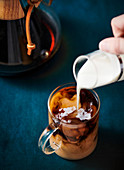 Cream being poured into a glass mug of hot coffee on a dark blue-green tablecloth.