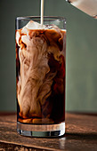 Cream being poured into a tall glass of iced coffee.