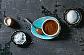 Homemade salted caramel sauce with grains of fleur de sel salt. Ingredients in ceramic bowls above