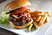 Juicy bacon cheeseburger deluxe with french fries and cornichon pickles