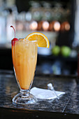Rum punch on a bar with an orange slice and marschino cherry garnish
