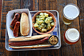 Sausasges, footlong hot dog, German potato salad, saurkraut and beer at a German-style beer garden