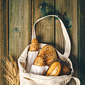 Eco bag with fresh bread on wooden background