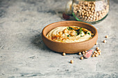 Large bowl of homemade hummus garnished with chickpeas, red sweet pepper, parsley and olive oil, middle east food