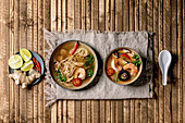 Variety of asian soups: Traditional spicy Thai tom yum kung and noodles soup with shiitake mushrooms, prawns
