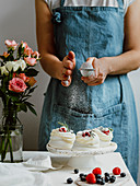 Woman in an apron sprinkles icing sugar through a sieve s on mini Pavlova cakes with fresh berries. Vertical composition with white marble tabletop and flowers in glass vase bottle
