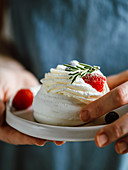 Woman hold plate with mini Pavlova cake decorated fresh berries and rosemary. Vertical composition. Copy space top.